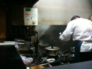 厨房で調理をする御主人